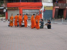 Ladies bring food each morning for the monks